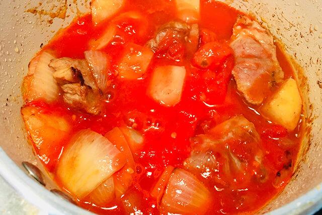 トマト缶、カレー粉、コンソメ、はちみつを入れて煮込んでいる様子
