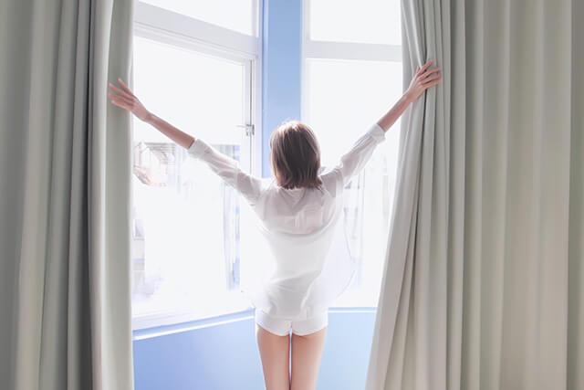 起床してカーテンを開ける女性