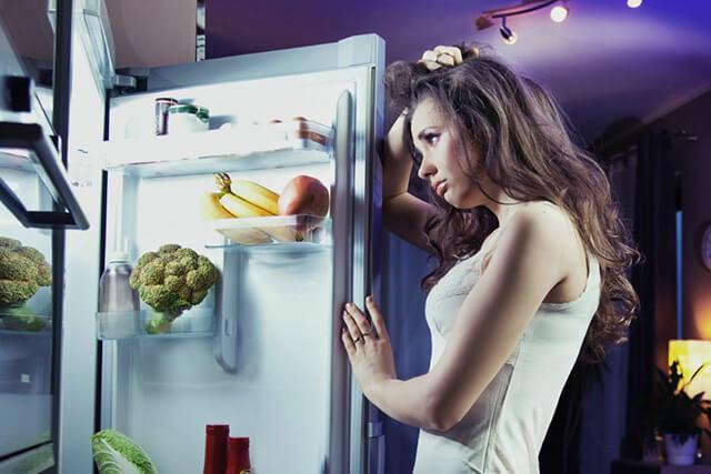 夜食を食べようと頭を抱える女性
